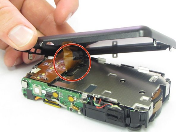 The screen is attached by a connection ribbon. Gently pull the casing and screen away from the camera body to disconnect the casing.