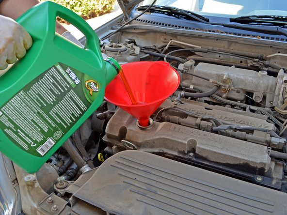 Image 1/2: Pour 4 quarts of 10W-30 oil into the engine. Use one hand to stabilize the funnel to help prevent spills.