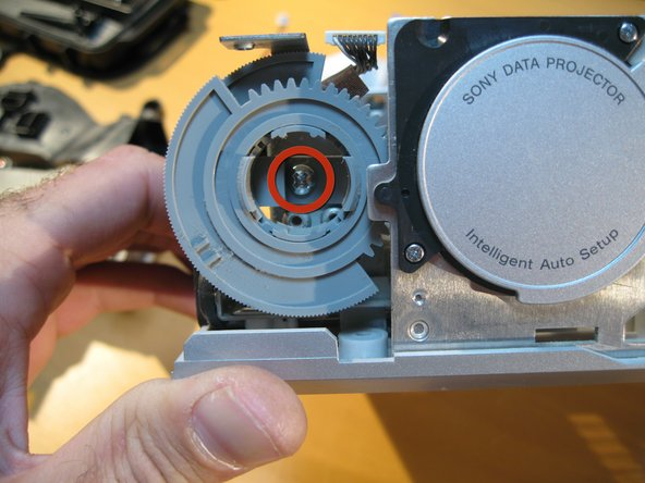 Image 2/3: Next to remove the screw holding the Autolens Cap to the rest of the unit.