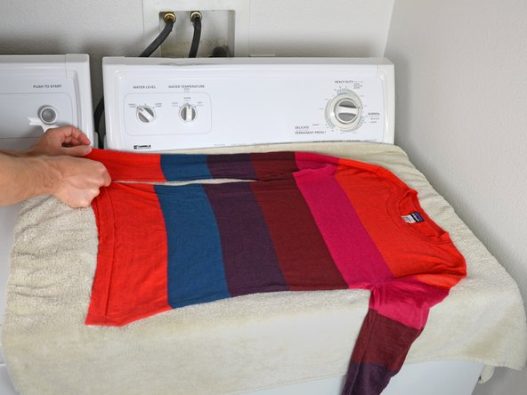 Lay the sweater out on the towel.