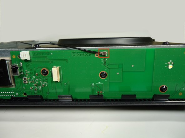 Using a spudger and a motion similar to the previous step, gently lift the antenna connector from the green board on the front.