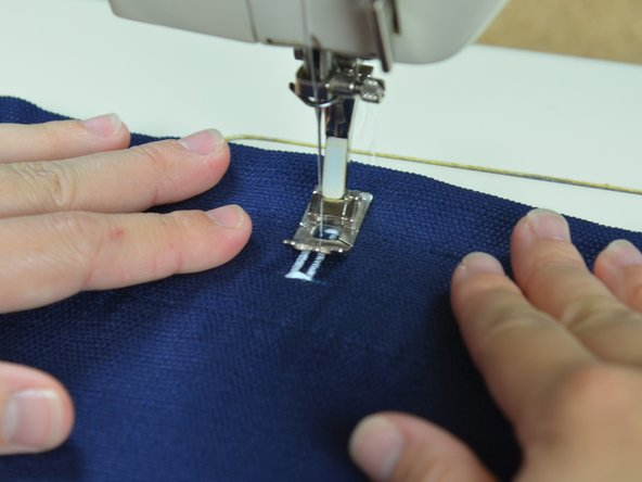 This setting backstitches to hold the thread in place. Sew a few more stitches, which will finish the buttonhole.
