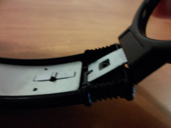 Pull the speaker clamp so that the metal lifts free of the headband.