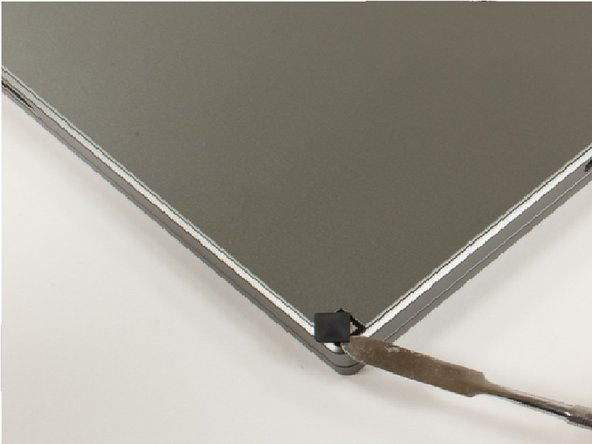 Image 2/2: Using a flat edge screwdriver, gently pull up to remove the rubber pads from the laptop to reveal the screws