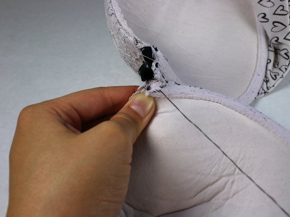 Pull the needle through the fabric until the knot at the end of the thread approaches the incision.