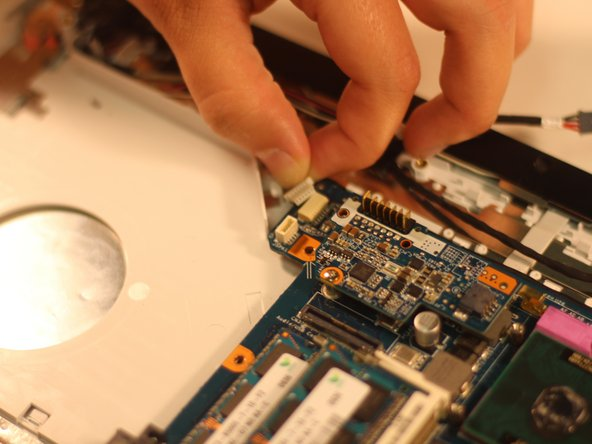 Using your fingers, grasp the three ribbon cable attachments (pictured) and gently pull on them to disconnect them from the motherboard.