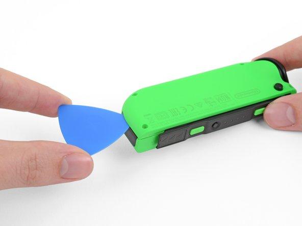 Setze ein Plektrum unter die untere Seite des Rückgehäuses. (Die Seite gegenüber des R und ZR Buttons.)