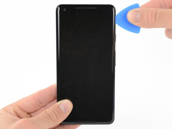 Slide the opening pick down the right side of the phone to separate the display adhesive.