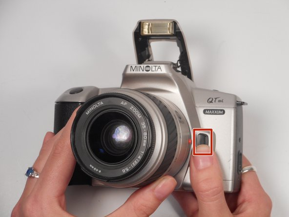 The lens release button is located on the right front side of the camera.