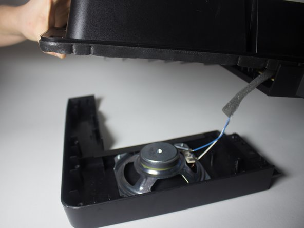 Gently remove the speaker and its compartment from the front of the keyboard.