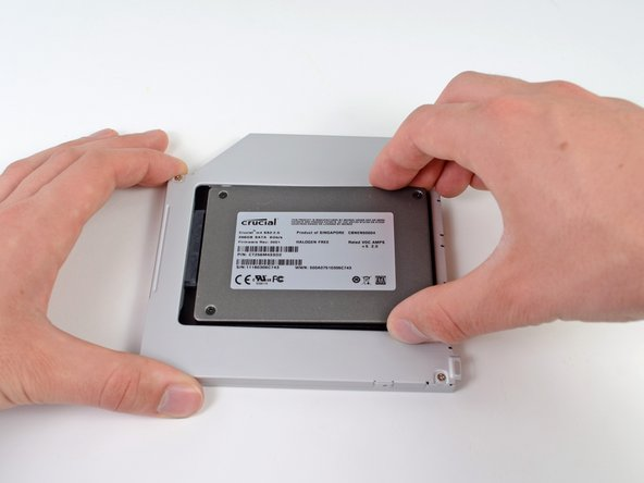Image 2/3: While firmly holding the enclosure in place with one hand, use your other hand to press the hard drive into the enclosure connectors.