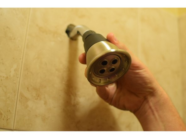 Finally, attach the shower head by turning the threaded end clockwise tightly into the teflon wrapped end of shower arm.