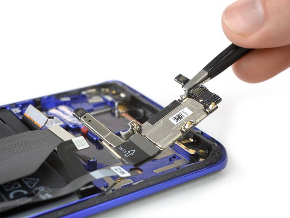 We use a pair of tweezers to dig out the last bits behind the motherboard.