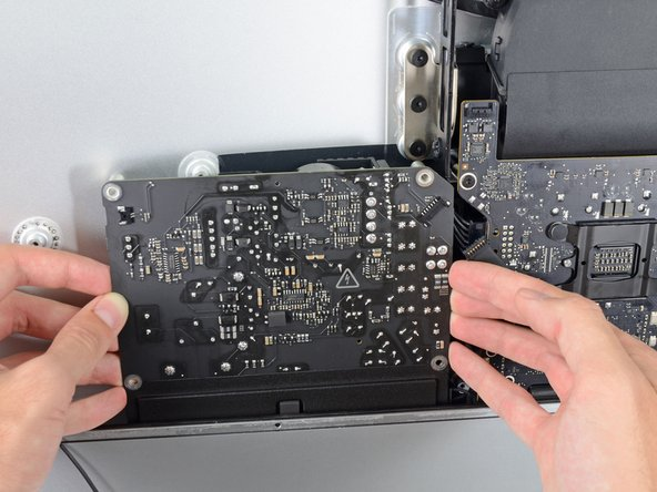 Move the power supply board towards the left edge of the case and up to free it from the notch in the logic board.