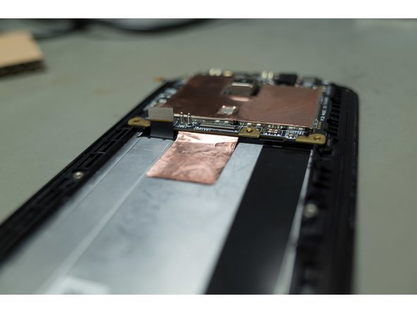 Once the battery is out you need to lift the copper sheet from the body of the phone, which is held in place with some mild adhesive. Use tweezers and lift from one corner gently, working your way slowly across the square piece.