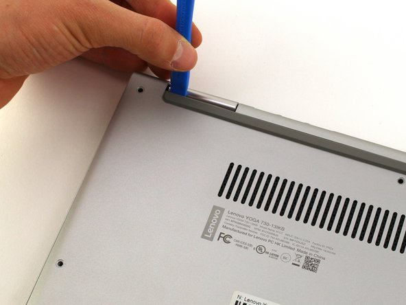 Slide a plastic opening tool underneath the back case near the screen hinges. Gently pry up on either side.