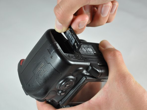 Image 1/2: Pop the battery door out by pulling the front tab up.