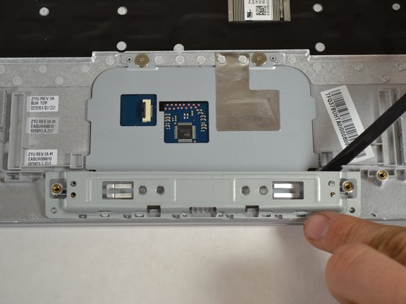 Use the spudger to push up on the metal cover below the touch pad until it reaches 90 degrees then pull up to detach.