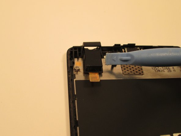 Image 1/1: Remove the motherboard and slide the headphone jack out of its slot.