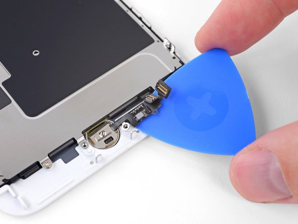 Use an opening pick to gently separate the adhesive holding the home/Touch ID sensor cable to the back side of the display panel.