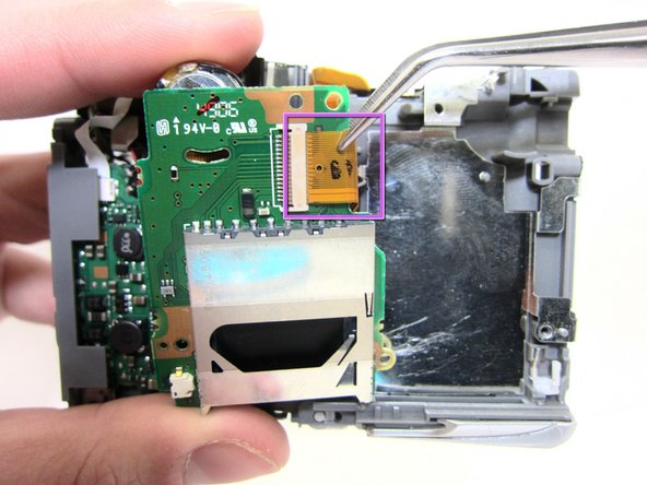 Remove the ribbon connecting the circuit board from the body of the camera using tweezers.