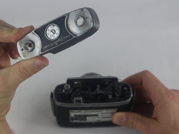While holding the camera with one hand, use the other hand to remove the top of the camera.