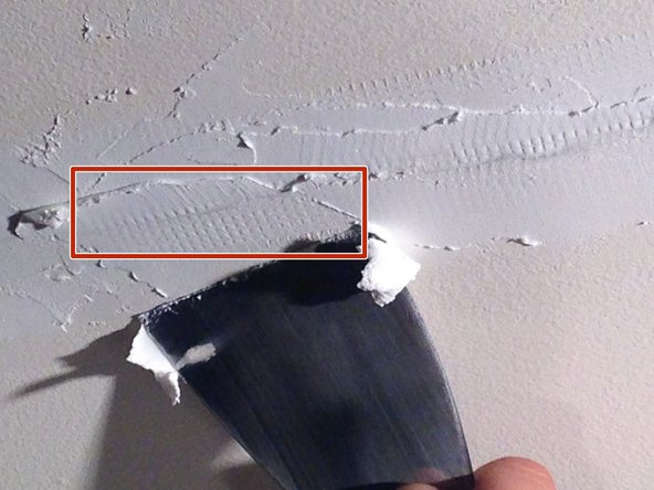 Spread drywall joint compound over the tape so that it appears flat.