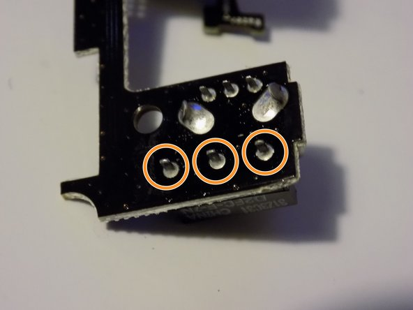 Image 2/3: Now de solder the 3 pass through post continue pulling the micro switch away from the circuit board