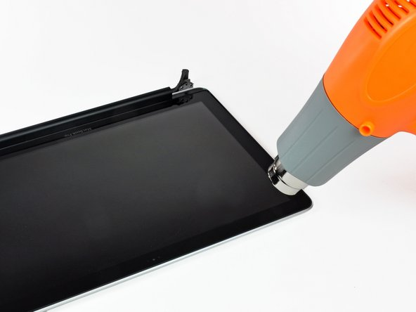 Image 1/2: Use a heat gun to soften the adhesive under the black strip near the upper left corner of the glass display panel.