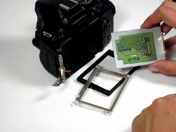 Remove the plastic bezel and metal bracket from the LCD itself to complete the removal process.