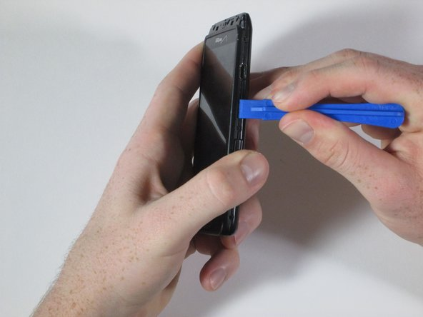 Run the plastic opening tool around the edge of the entire device to pry apart the front of the phone from the back.