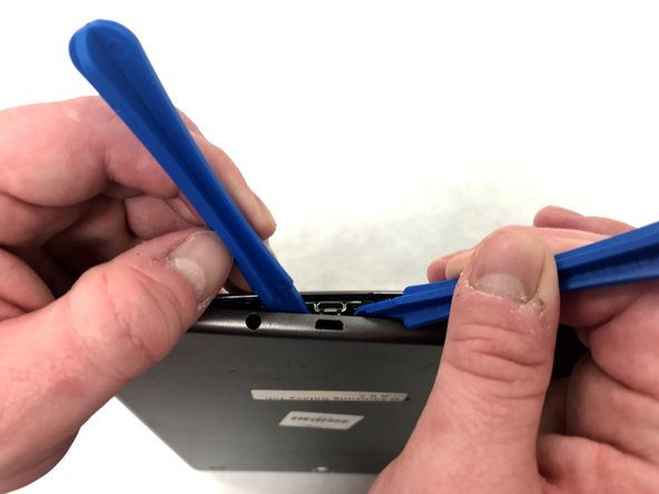 Insert a second iFixit opening tool along the edge and begin to pry open the back cover a little with each one.