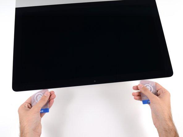 Les deux cartes étant insérées près des angles de l'iMac, comme illustré, tournez-les doucement pour élargir l'interstice entre l'écran et le boîtier.