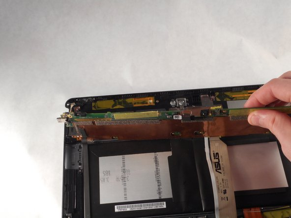 Once the mother board is relieved from the glue, use your hand to lift the motherboard up and to the opposite end of the back panel.