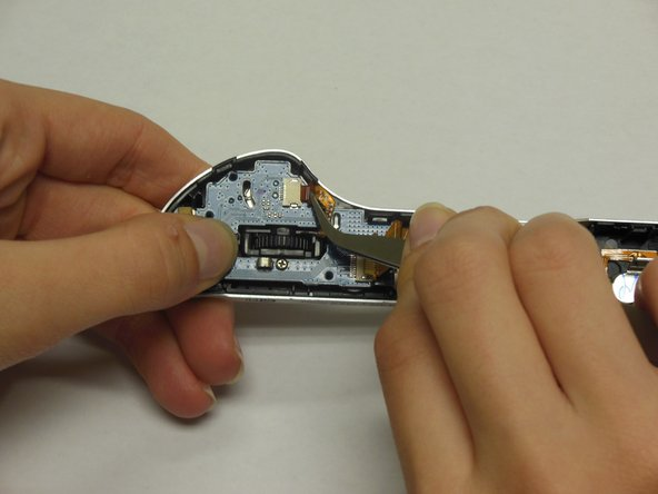 Using tweezers, gently remove the ribbon cable attached to the jog dial.