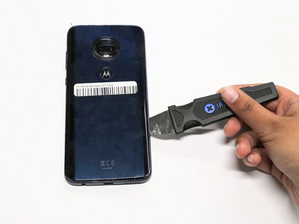 Loosen the adhesive by cutting along the sides of the phone with the Jimmy Knife and prop open the back.