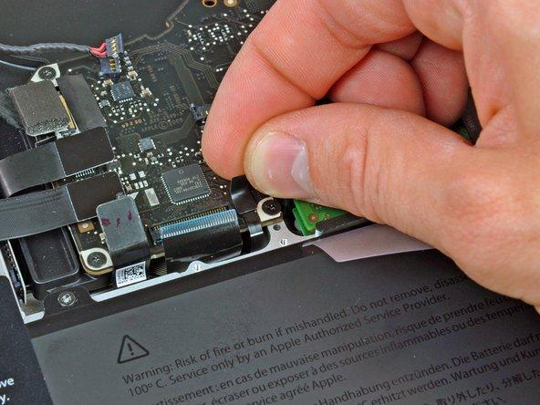 Décollez le petit morceau de bande adhésive noire sur la prise de la nappe du rétro-éclairage du clavier.