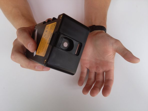 Flip device upside down. Hold the device and tap into your other hand with varying force to remove battery.