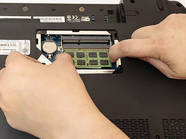 Push the two bottom tabs outwards and the bottom stick of RAM will pop up. Gently remove the bottom stick of RAM by pulling it out.