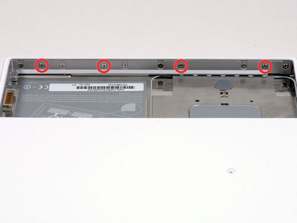 Image 1/1: Remove the four indicated Phillips screws from the front wall of the battery compartment. When working from the left, remove the 2nd, 4th, 7th and 9th screw.