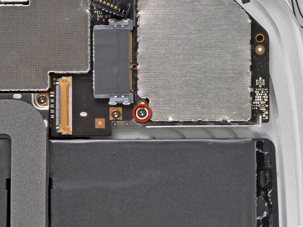 Remove the single T5 Torx screw securing the communications board to the rear case.