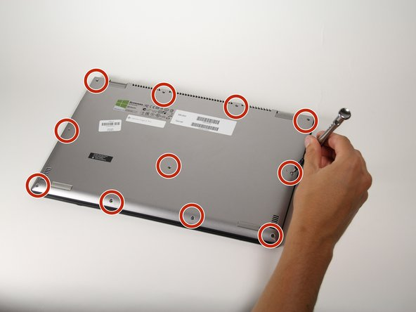 """Image 1/1: Using a T5 Torx screwdriver, remove the eleven 1/4"""" screws from the back of the laptop."""