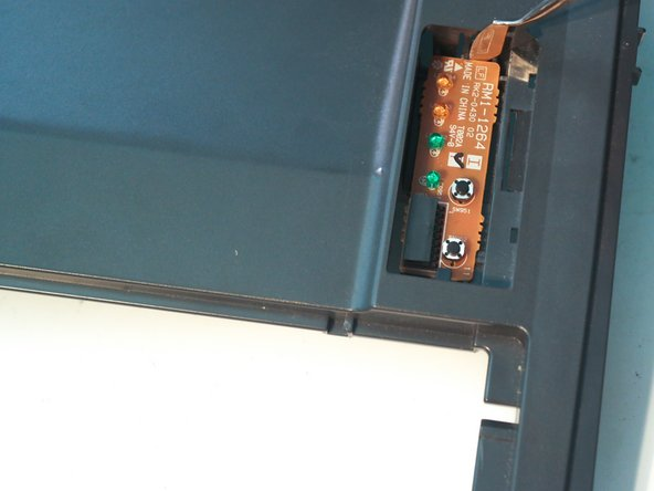Use a metal spudger to remove the control panel and its circuit board from the top cover.
