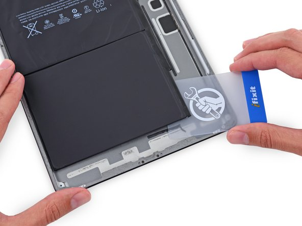 Insert a plastic card under the lower battery cell, at the lower right-hand corner.