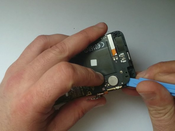 With a plastic tool gently release the mother board and remove it.