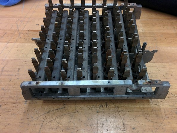 Turn the keyboard assembly over, and remove the frame by lifting up a bit and then out. There are pins on the frame which allow lock bars for each row to pivot.