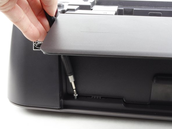 In the front of the printer, open the tray where the paper comes out and remove the two 13 mm screws located under the top of the printer.