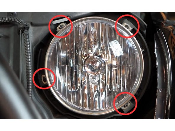 Remove the four (4) screws that are holding the metal bracket ring around the headlights.