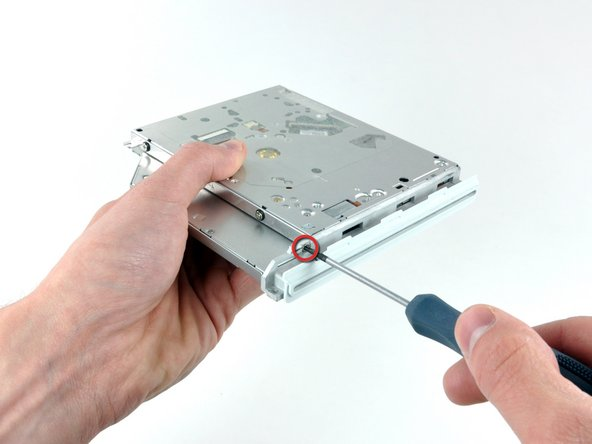 Remove the single Phillips screw securing the bezel on the front of the optical drive.