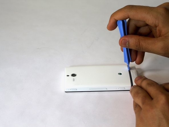 Set the phone screen down on a clean flat surface.